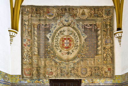 fiestas: Tapestry with the coat of arms of Queen Isabella of Portugal at the Sala de las Fiestas in the gothic palace of the Alcazar of Seville, Spain