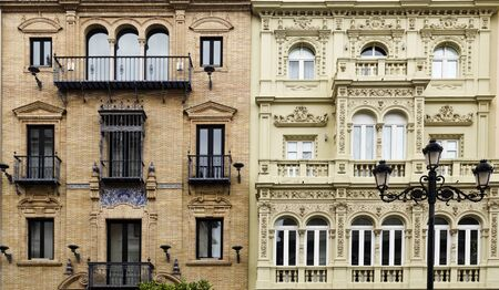 contiguous: Detail of contiguous buildings with two different classic architectural styles in Seville, Spain