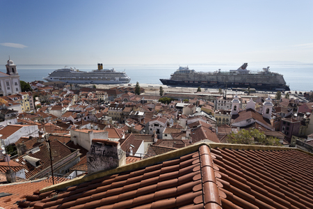 docked: View over the roofs of the old city towards the cruise ship terminal with two ships docked in Lisbon, Portugal