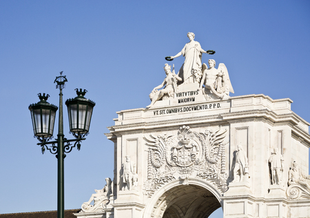 taught: Detail of the Rua Augusta Triumphal Arch, depicting the female allegory of Victory  rewarding Valor and Genius, in Lisbon, PortugalTranslation: To the virtues of our ancestors who taught us everything paid for at public expense