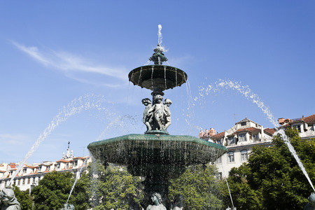 adorning: Bronze fountain adorning Rossio Square, located in the Pombaline Downtown and a main square in Lisbon, Portugal