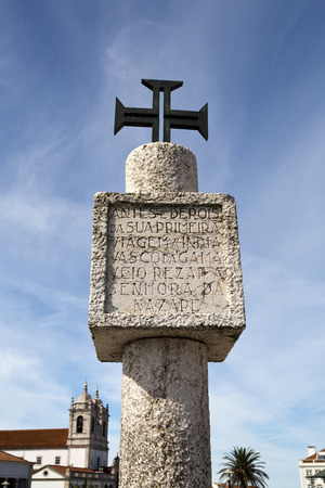 Limestone memory pillar with inscription and Order of Christ Cross located on the hilltop O Sitio overlooking Nazare, Portugal.