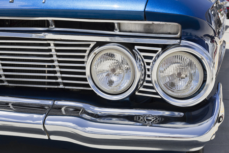 Detail of the front grill of a 1961 Chevy Bel Air car showing the Chevrolet badge and the headlights, in Brisbane, Australia