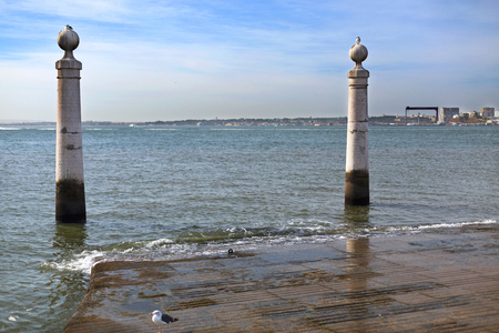 gently: Cais das Colunas is a marble flight of steps, flanked by two water stained marble columns, which runs gently into the Tagus River in downtown Lisbon, Portugal Stock Photo