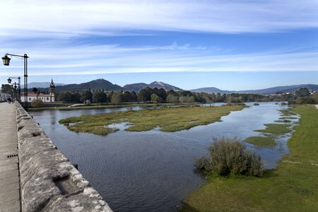 View of the Limia River seen from the medieval bridge in Ponte de Lima, Portugal Stock Photo