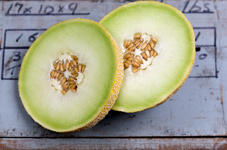 Detail of a ripe golden honeydew melon with its succulent, velvety and sweet flesh on an antique farm timber box