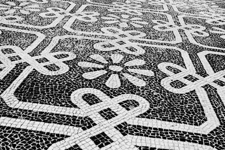 Traditional style Portuguese pavement, designed with black and White stones of basalt and limestone, used in pedestrian areas of Portugal Stock Photo