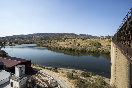The Douro River at the location of the abandoned truss road-rail bridge with the rail track above the roadway in Pocinho, Douro region, Portugal