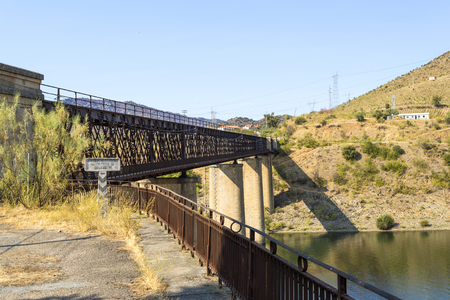 Abandoned truss road-rail bridge with the rail track above the roadway crossing the Douro River in Pocinho, Douro region, Portugal