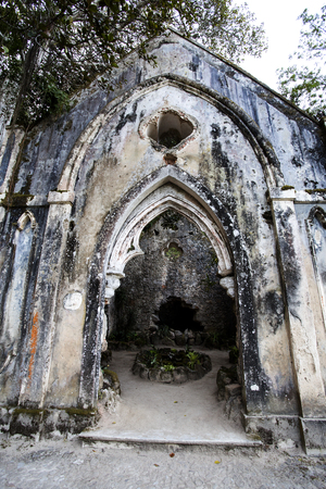 View of the fake ruins of a chapel, a popular romantic concept of the 1800s, being overrun by an Australian Banyan tree (ficus macrophylla) near Sintra Stock Photo