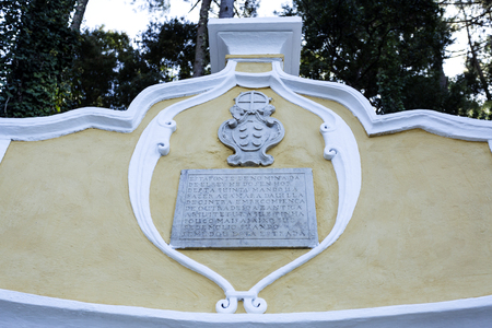 King Fountain has a semi-circular shape, a water tank with benches and two spouts. On top is a coat of arms and a plate with an old Portuguese language inscription Editorial