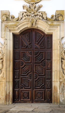 Entrance hand carved wood door to the baroque chapel of the Mateus Palace in Vila Real, Portugal