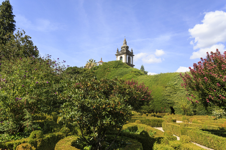 The superb gardens of the Mateus Palace with a glance of the chapel dome and the bell tower, in Vila Real, Portugal