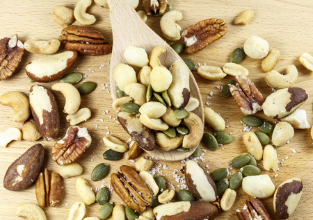 Variety of nuts: Brazil nuts, pecan, peanuts, cashew, macadamia, pepitas, coconut on a wooden spoon on board Stock Photo - 100780972