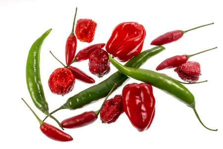 Variety of red and green chili peppers (Capsicum annuum and Capsicum chinense), including Green Cayenne, Birds Eye, Habaneros and Carolina Reaper, from mild to extremely hot pungency.