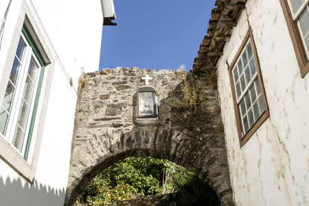 Remain of one of the three agtes of the medieval gothic castle of Vinhais, Portugal. Inside the niche is a statue of St Anthony and above a cross