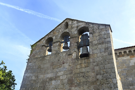 View of the separate belfry with three bells of the Romanesque Church of St Peter in Roriz, Portugal