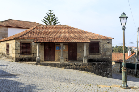View of the old granite stone house with three columns forming the verandah, in front of the Church of St Peter of Roriz, Portugal
