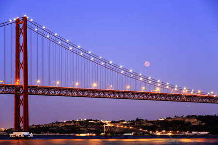 View of the lunar eclipse, the longest blood moon of the 21st century, over the 25th April Bridge in Lisbon, Portugal