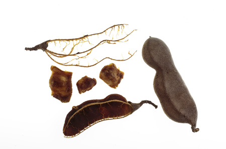 View of a whole tamarind fruit and the pulp, seeds and fibers of a broken tamarind (Tamarindus indica) pod-like fruit Stock fotó