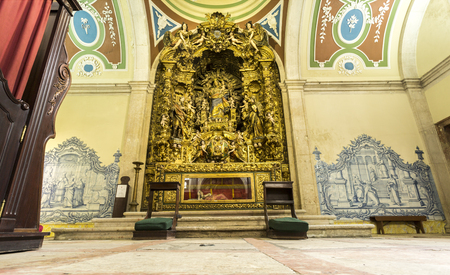 The Chapel of Our Lady of the Rosary, or the France, has a great Baroque altar with rich gilded carvings, flanked by traditional blue and white tile panels, in Lisbon, Portugal