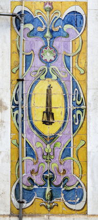 Magnificent coloured tiles, or azulejos, covering the wall panels between the entry doors of a commercial property in downtown the old city of Lisbon, Portugal Stock Photo