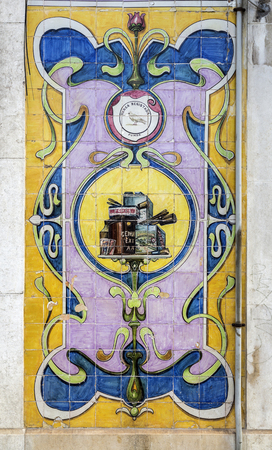 Magnificent coloured tiles, or azulejos, covering the wall panels between the entry doors of a commercial property in downtown the old city of Lisbon, PortugalTransl: Registered Brand DOVE Stock Photo