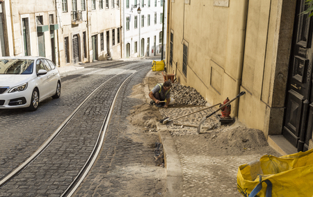 View of a traditional professional paviour person laying cobblestones on a sidewalk of a street in downtown Lisbon, Portugal