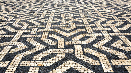 Typical Portuguese cobblestone pavement creating balck and white patterns using basalt and limestone cobbles, in Lisbon, Portugal