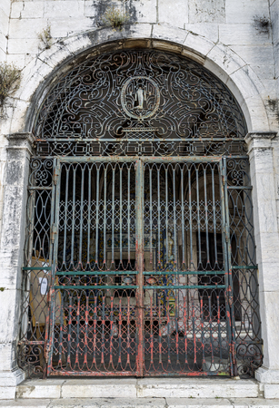 It is believed St Amaro healed broken legs and arms. In this gate of the 18th century, a leg is the main feature of the decoration. In Lisbon, Portugal Stock fotó - 119826418