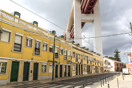 Quiet residential street directly underneath the access to the 25th of April suspension bridge in Lisbon, Portugal Editorial