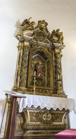 View of the gilded side altar in the Chapel of Saint Amaro with a statue of Saint Amaro peregrine, in Alcantara, Lisbon, Portugal