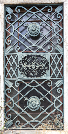 Detail of the elaborated iron grill covering the windows of each side of the entrance portal of the Palace Condes da Ponte built in early 18th century in Alcantara, Lisbon, Portugal