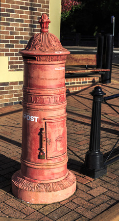 View of an old traditional red mail box on a street in Armidale, NSW, Australia
