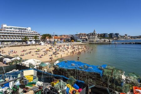 View of the crowded pretty little beach named Praia do Pescador along the famous fishing traps of the Cascais Bay, nearby Lisbon, Portugal