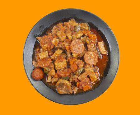 Pork belly and chorizo stew on orange background. Imagens