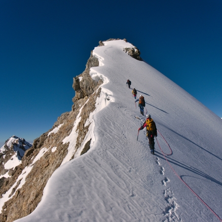 to climb: Mountaineers climbing a mountain Stock Photo