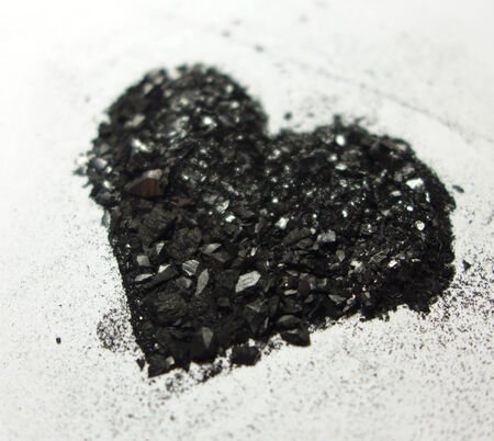 Shimmering heart made form graphite dust from perspective photo