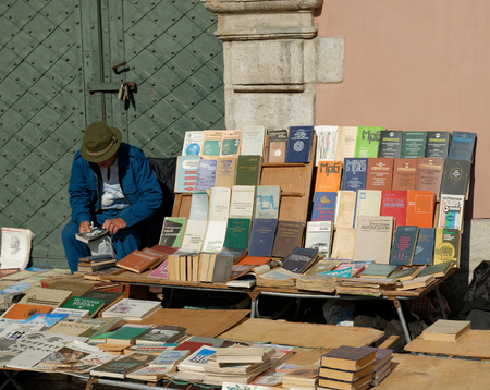 LVIV, UKRAINE - OCTOBER 4, 2014: Book flea market near the monument of Ivan Fyodorov. Man selling his books and looking at second hand book on 4 October 2014, Lviv, Ukraine. 新聞圖片
