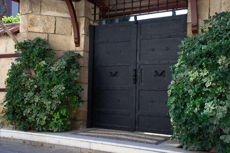 Black metal door with green bushes in Antalya