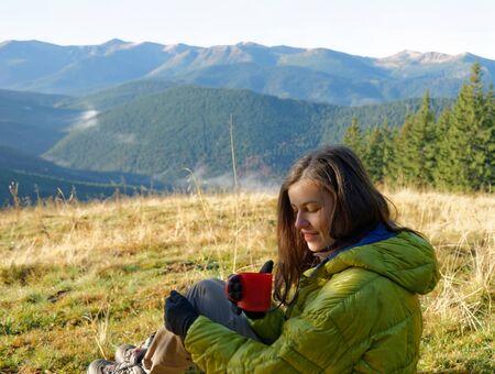 Portrait des Mädchens in gelb Daunenjacke sitzen mit roten Tasse heißes Getränk im Herbst Bergen mit Nebel in den Tälern Standard-Bild