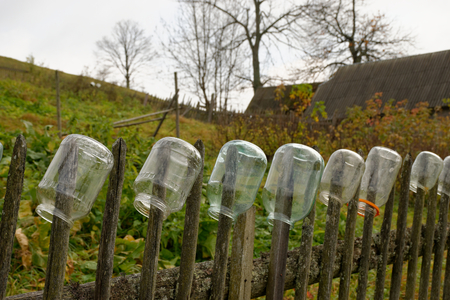 glass fence: Glass jars hanging on a fence in a village