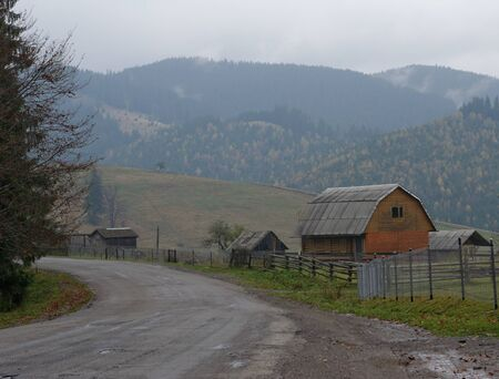 Traditional village house standing hear the road in Carpathians, Ukraine Imagens