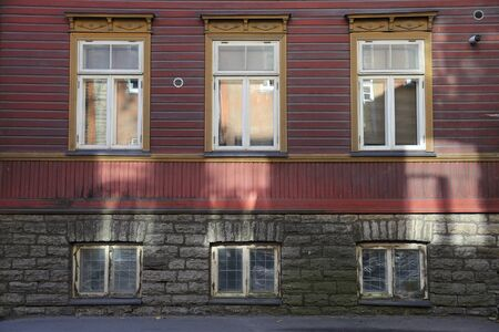 view of a wooden doorway: Sunlight reflections from windows on historic building in Tallinn Stock Photo