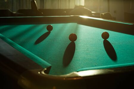 snooker hall: Table with billiard and tree balls silhouettes with long shadows in the light of sunset