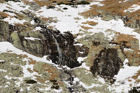 Waterfall in the winter mountains with texture of snow and rock