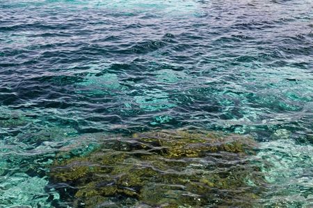 emerald: Clear waters of mediterranean sea with turquoise and emerald colors being vibrant next to the stones with gold tone