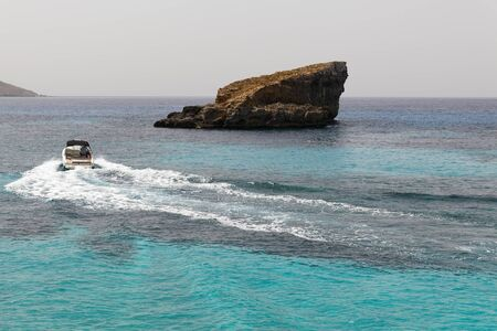 clear waters: Motor boat in the blue lagoon with azure clear waters. Blue lagoon is on the shore of island Commino in Malta