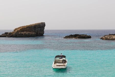Motor boat in the blue lagoon with azure clear waters. Blue lagoon is on the shore of island Commino in Malta