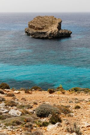 Lonely island in the Mediterranean sea near island Commino in Malta with turquoise waters and vibrant golden sand and land